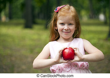 Little red-haired girl holding a red apple on a background...