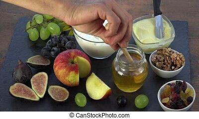 honey is deposited on yogurt - honey, figs, grapes, dried...