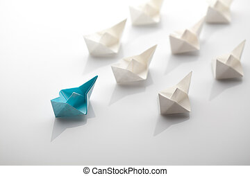 paper ship - Leadership concept using blue paper ship among...