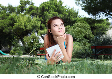 school girl at the park with e book, look up