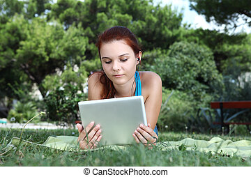 school girl at the park with tablet and earphone