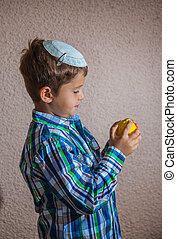 The seven year old boy in skullcap is holding citrus -...