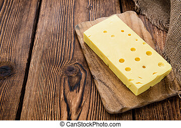 Block of Cheese close-up shot on vintage wooden background
