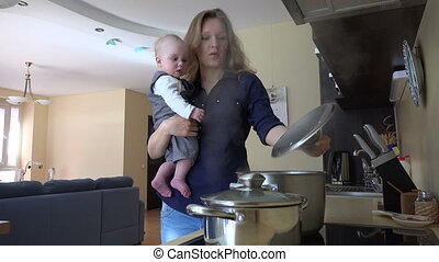 mother baby cook pot - Nanny with infant baby in hands...