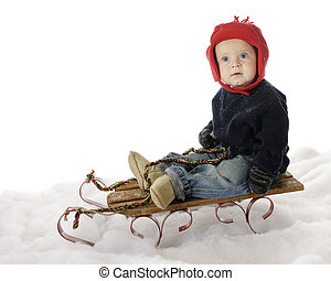 Lets Get Going - An adorable baby boy sitting on a sled in...