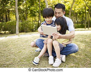 asian father and children using tablet outdoors - asian...