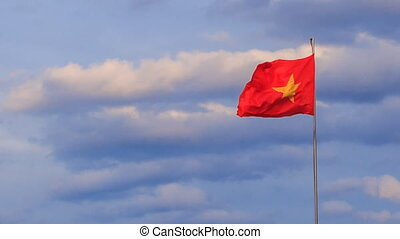 view of Vietnamese banner flapping in wind at sunrise -...
