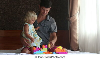 little blonde daughter plays toy constructor with father on...