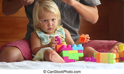 little girl plays with toy constructor father brushes her...
