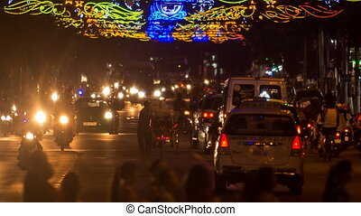 cars motorbikes up and down street against upper illumination