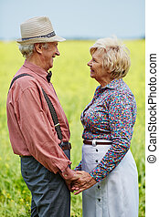 Attraction - Senior man and woman holding by hands and...