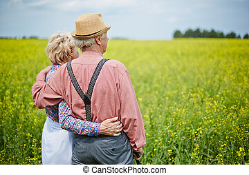 Couple in the country - Rear view of senior couple standing...