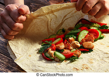 Shawarma - Mens hands wrapping traditional shawarma wrap...