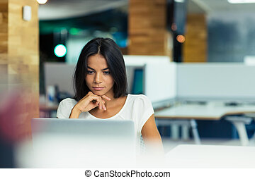 Businesswoman using laptop in office - Portrait of a serious...