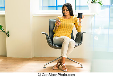Businesswoman sitting on office chair - Happy businesswoman...
