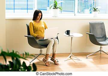Businesswoman sitting on office chair and using laptop -...