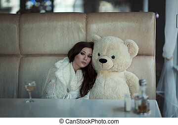 The sad girl sits at a table with toy bear. - The sad girl...
