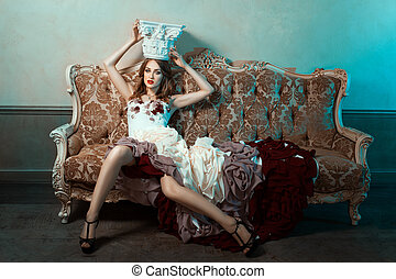Girl on the couch ball gown and trying crown. - Girl sitting...