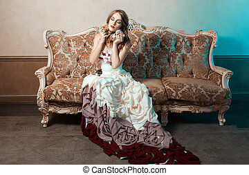Girl ball gown sitting on the couch and cuddle kittens -...