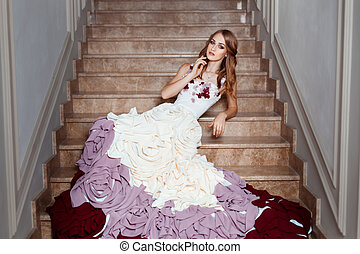 Girl in a ball gown lying on the steps. Dress with a train.