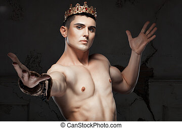 Young man with a crown on his head His athletic body