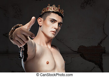 Young man with crown on the head pointing her finger - Young...
