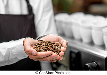 Holding coffee beans - Male hands holding roasted coffee...