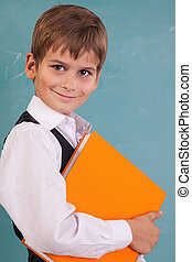 ?ute schoolboy is holding an orange book against school...