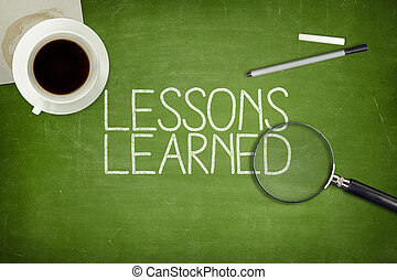 Lessons learned concept on green blackboard with coffee cupt...