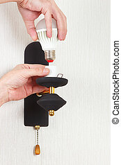 Hand unscrews led bulb in luminaire on white wall - Hand...
