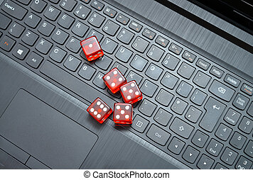 online gambling - five red casino dice over the laptop...