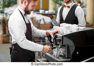 Barista making coffee with waiter - Handsome barista in...