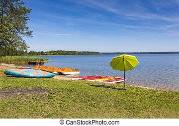 Colorful kayaks moored on lakeshore, Goldopiwo Lake, Mazury,...