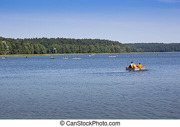 Couple kayaking on Goldopiwo Lake, Mazury, Poland.