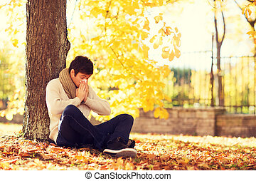 ill man with paper tissue in autumn park - healthcare and...