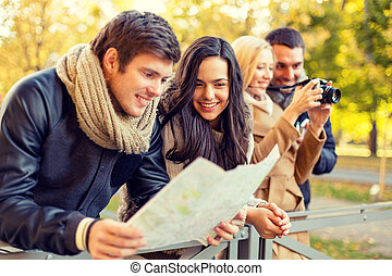 group of friends with map and camera outdoors - travel,...