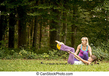 Woman working out with a personal trainer outdoors on a...