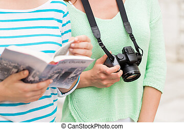 close up of women with city guide and camera - tourism,...