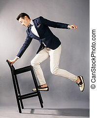 young handsome businessman in studio with chair jumping,...