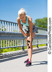 young woman with injured knee or leg outdoors - fitness,...