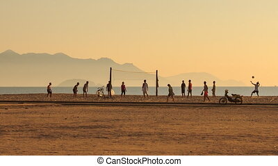 people play volleyball on beach against sea hills at sunrise