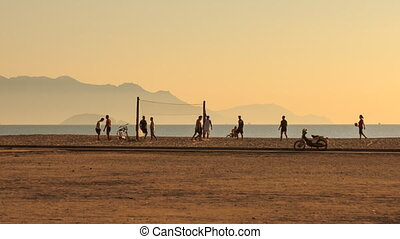 people play volleyball on beach motorbikes pass by at dawn