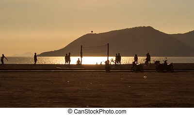 men play volleyball on beach against sunlight path at sunrise
