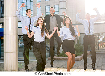 Business Jump - Group of young business people jumping in...