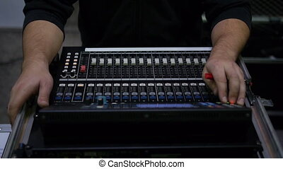 Man at a mixing desk - Black dressed man doing the settings...