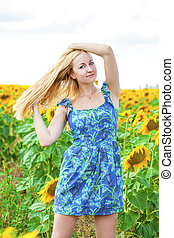 Portrait of a beautiful young blonde woman in blue dress on...
