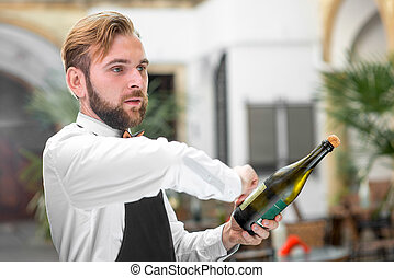 Barman opening bottle with sparkling wine - Handsome barman...