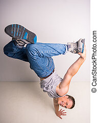 Breakdancer - Handsome breakdancer standing on his hand at...