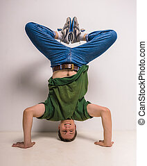 Breakdancer - Handsome break dancer standing on his head and...
