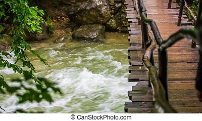 Man Walking On Bridge Hanging Above Rough River - In the...